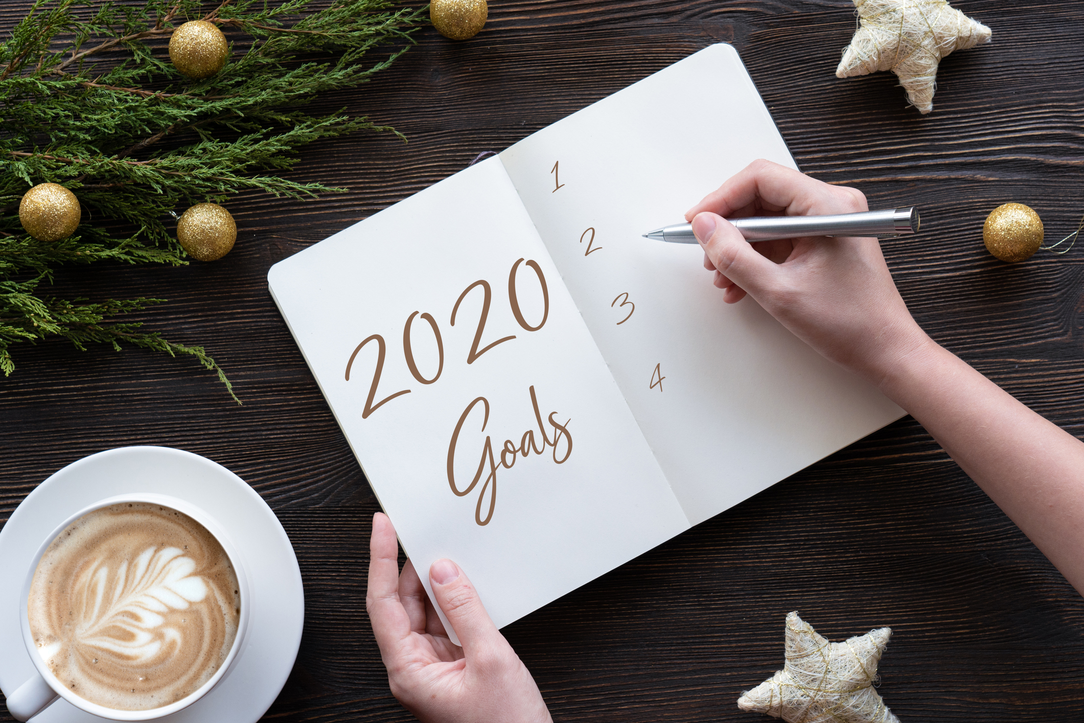 Female hands write new year goals in notebook on brown wooden table, flat lay