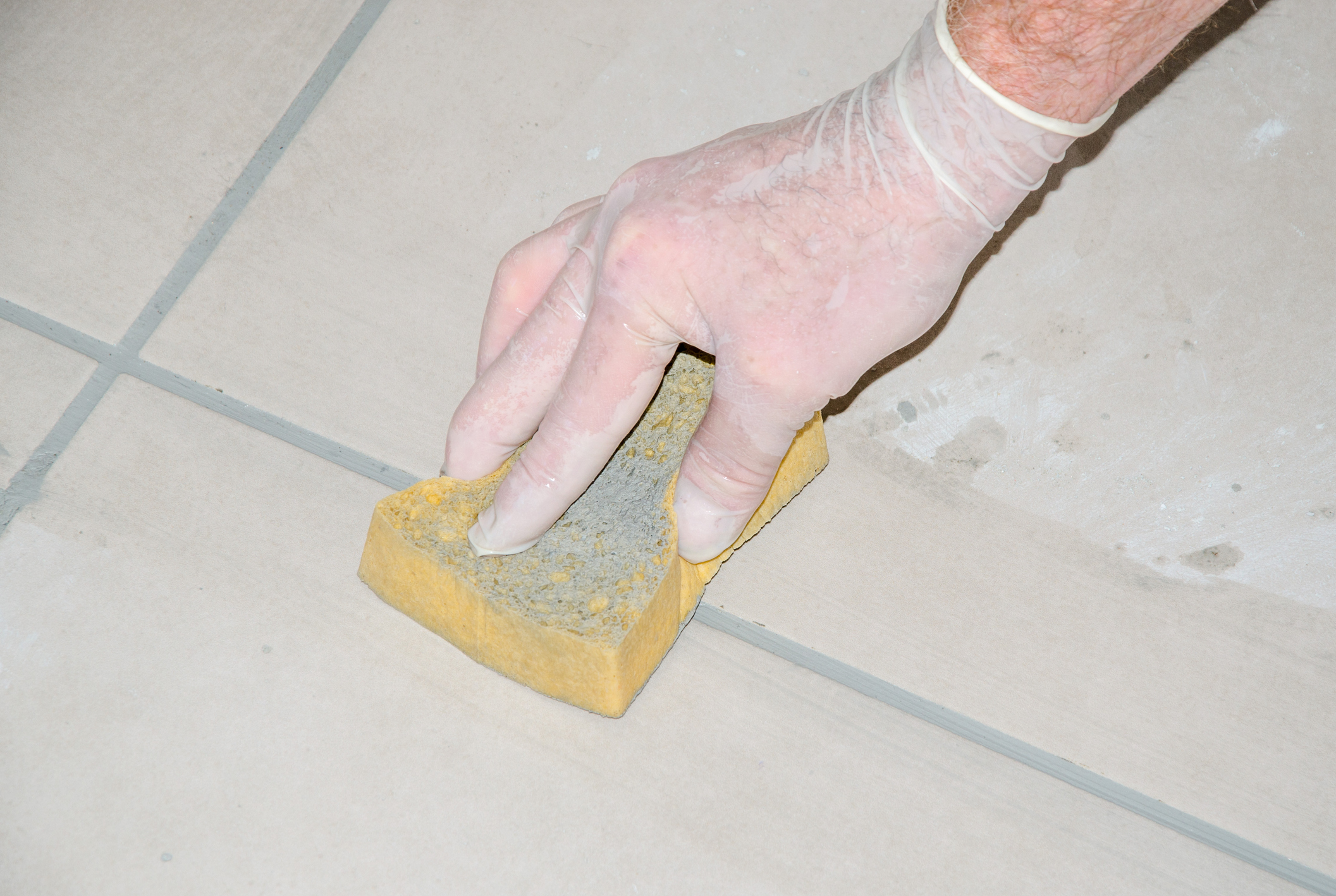 Tiler smoothing tile joints with a sponge