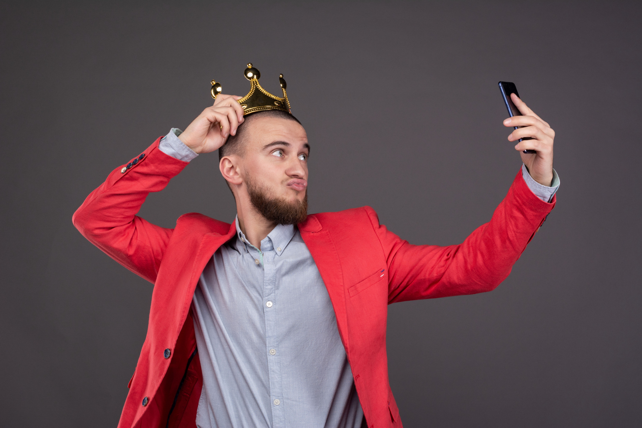 Young bearded handsome man in gold crown taking selfie looking at smartphone