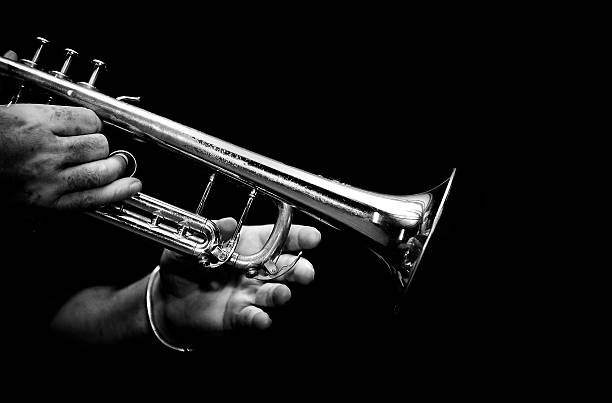 trumpeter playing his trumpet in black and white