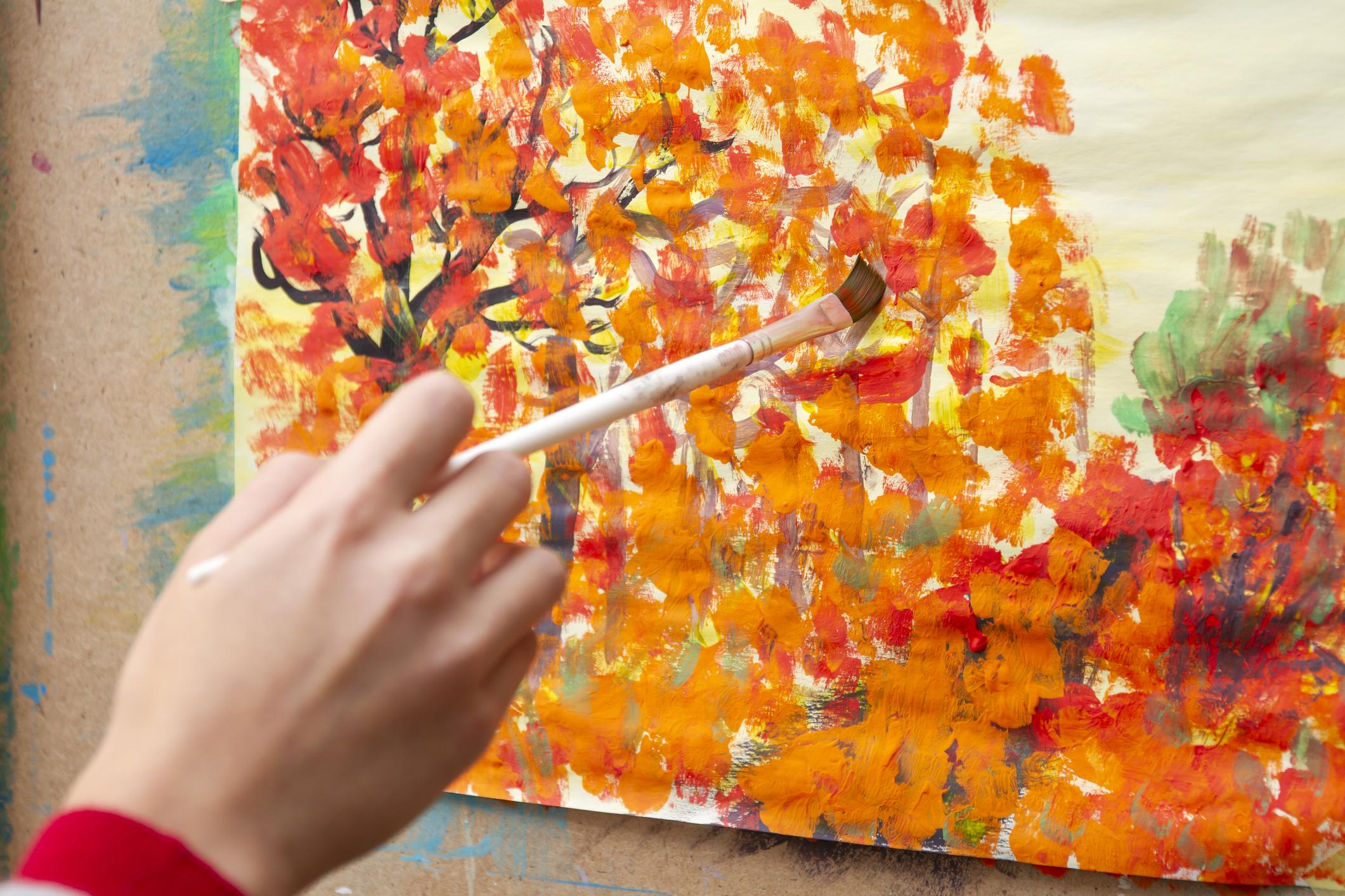 Young artist paints orange autumn trees on canvas